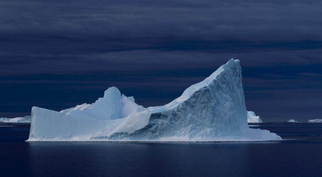 A stark white iceberg against a deep blue still ocean