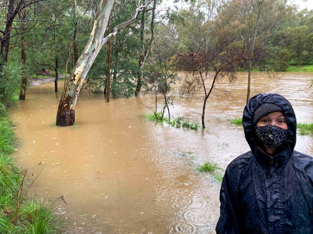 The author in her raincoat, with the Yarra breaking its banks behind her