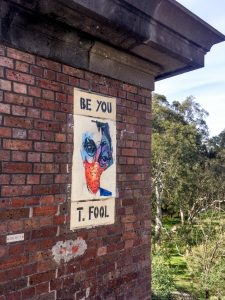 some street art under a bridge: a picture with the words BE YOU T. FOOL