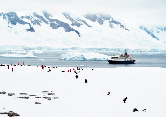 Antarctic tourists and their icebreaker are dwarfed by massive ice mountains in a sea of white.